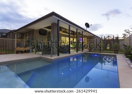 Swimming pool and outdoor entertaining area in stylish home at dusk - stock photo