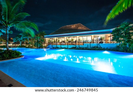 Swimming pool and restaurant at the luxury caribbean resort at night, dawn time. Mexico. - stock photo