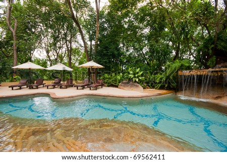 Swimming pool and umbrella - stock photo