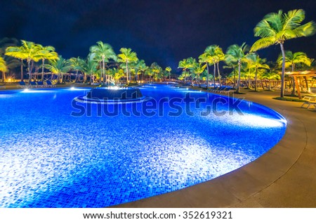 Swimming pool at a luxury caribbean resort at night, dawn time.