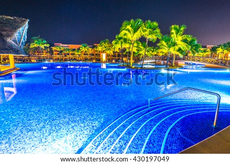 Swimming pool at a luxury caribbean, tropical resort at night, dawn time. - stock photo