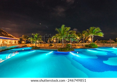 Swimming pool at luxury caribbean resort at night, dawn time. Mexico. - stock photo