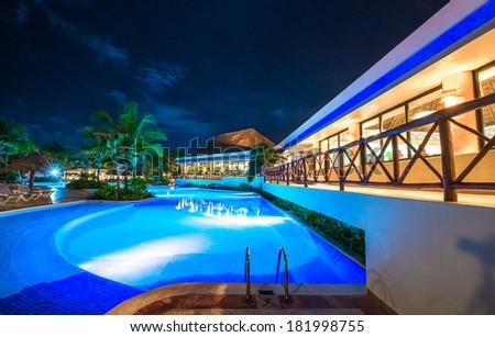 Swimming pool at promenade and restaurant at luxury caribbean resort at night, dawn time. Bahia Principe, Riviera Maya, Mexico. - stock photo