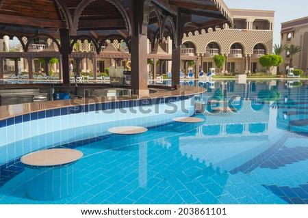 Swimming pool bar in luxury tropical hotel resort - stock photo