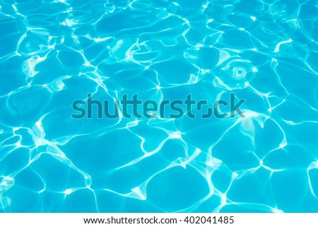 Swimming pool blue water reflecting the sun rippled details. - stock photo