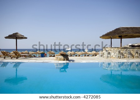 swimming pool by sea at resort hotel luxurious greek island with stone bar