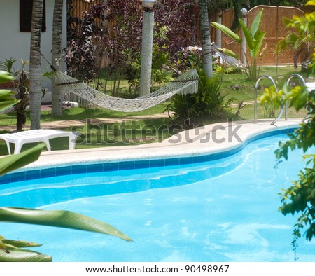 swimming pool in a tropical garden with hammock - stock photo