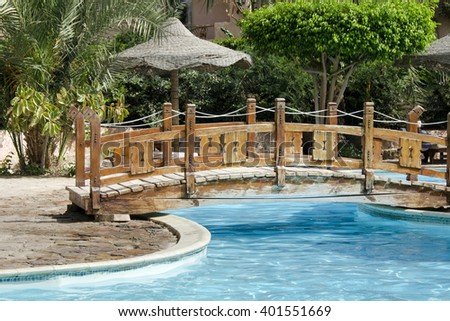 swimming pool in a tropical hotel resort with palm trees