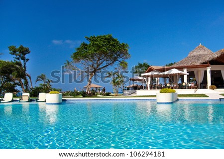 Swimming pool in caribbean resort - stock photo