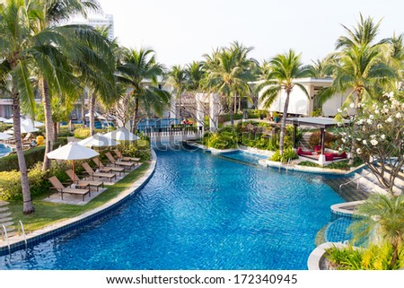 Swimming pool in residential garden with waterfall and chairs - stock photo