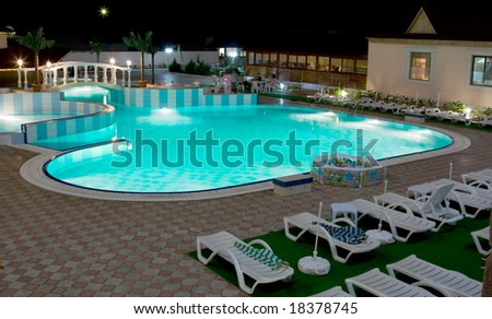 Swimming-pool in resort with around deck-chairs for relaxing in blue sea water night scene - stock photo