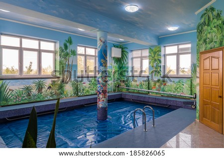 Swimming pool interior with tropical wall paintings
