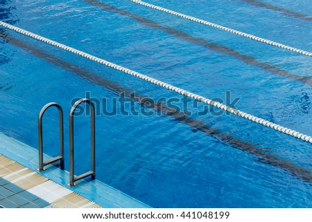 Swimming pool ladder and lane ropes - stock photo