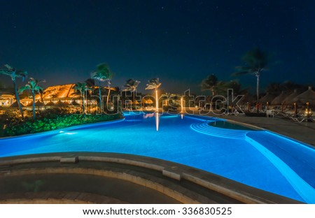 Swimming pool of a luxury caribbean, tropical resort, hotel at night, dawn time.