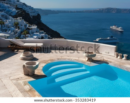 Swimming pool of a luxury hotel with sea view. White architecture of a Santorini island, Greece. - stock photo
