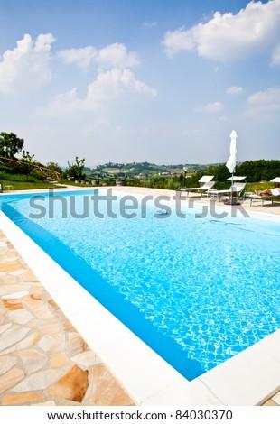 Swimming pool of an Italian beauty farm in the middle vineyards, Monferrato area, Piemonte region. - stock photo