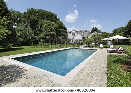 Swimming pool of luxury home with deck chairs