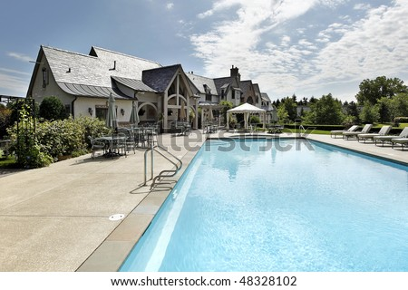 Swimming pool of luxury home with large deck - stock photo