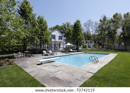 Swimming pool outside luxury home with diving board - stock photo