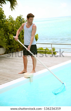 Swimming-pool service man cleaning water - stock photo