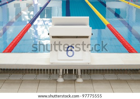 Swimming pool starting place with clearly marked lanes - stock photo