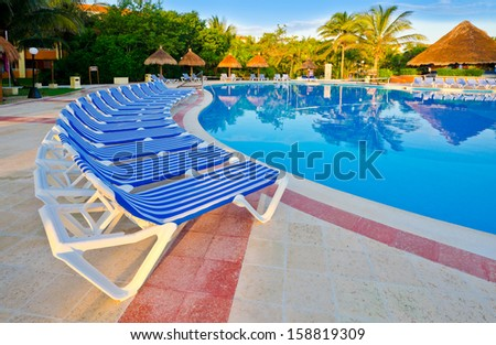 Swimming pool surrounded by chairs at the luxury mexican resort. Bahia Principe, Riviera Maya. - stock photo