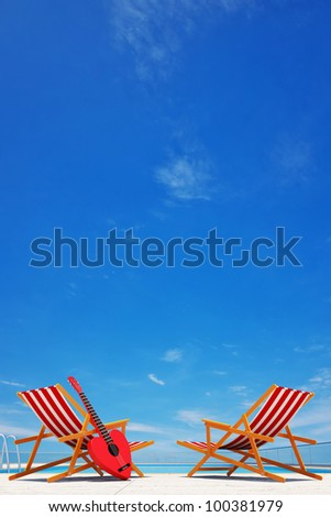 swimming pool with 2 beach chairs & guitar - stock photo