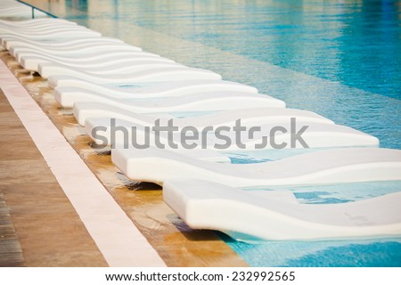 Swimming pool with beach lounge - stock photo