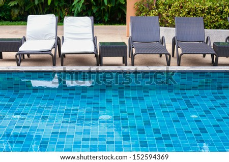 Swimming pool with black and white beach chairs - stock photo
