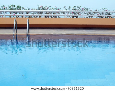 Swimming pool with blue water on terrace of condominium - stock photo