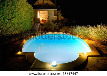Swimming-pool with candles at night - stock photo