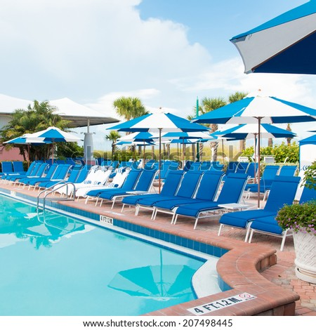 Swimming pool with chaise lounge and umbrellas at tropical resort - stock photo