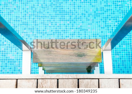 Swimming pool with close up wooden stair close up - stock photo