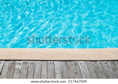 Swimming pool with concrete and wooden deck as a background - stock photo