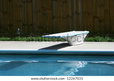 Swimming pool with concretes deck and diving board