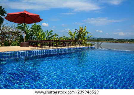 Swimming pool with daybed and red umbrella  in Chiangrai ,Thailand