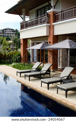Swimming pool with deck chairs and umbrellas. - stock photo