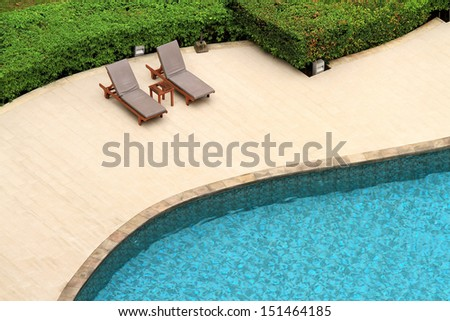 Swimming pool with deckchairs - stock photo