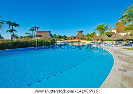 Swimming pool with deep blue sky and dark blue water at the luxury mexican resort. Bahia Principe, Riviera Maya.