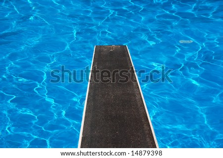 Swimming pool with diving board and reflections - stock photo