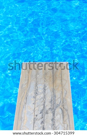 Swimming pool with old wooden diving board - stock photo