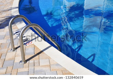 Swimming pool with palm tree shadows