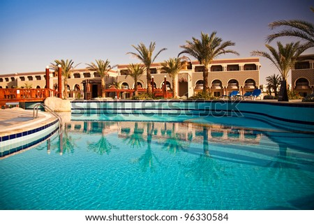 swimming pool with palm trees at morning, Hurghada, Egypt - stock photo