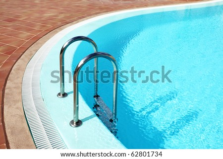 Swimming pool with stair at a hotel - stock photo