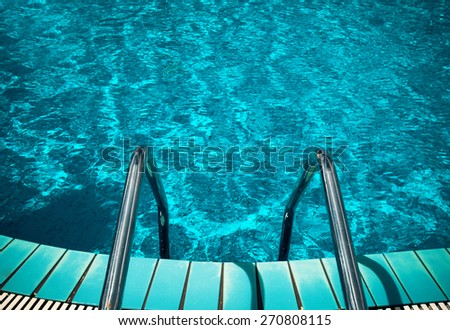 Swimming pool with stair at hotel close up - stock photo