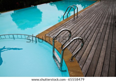 Swimming pool with stair at hotel in the morning time - stock photo