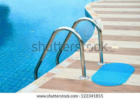 Swimming pool with stair close up with reflections background. - stock photo