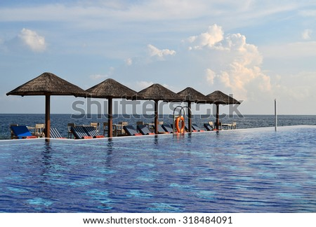 Swimming Pool with Sun chairs and Natural Umbrellas beside the sea - stock photo