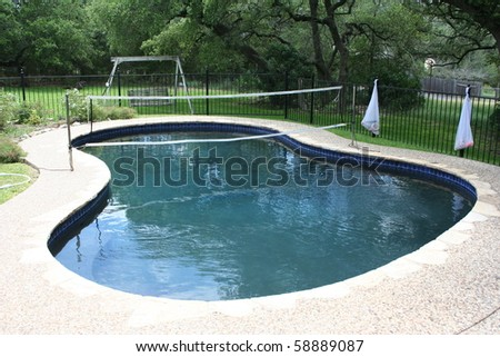 Swimming pool with volleyball net in a backyard - stock photo