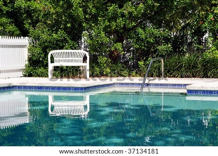 Swimming Pool With White bench - stock photo